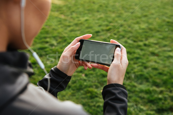 Cropped picture of female runner chatting Stock photo © deandrobot