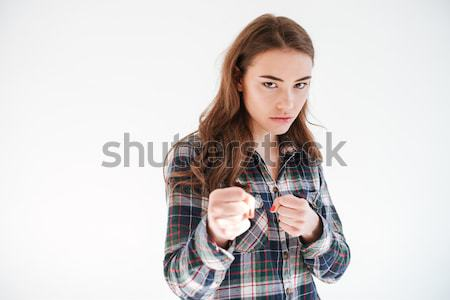 Angry concentrated young woman with fists ready to fight Stock photo © deandrobot