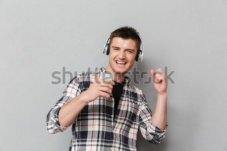 Scared frightened young woman in plaid shirt standing and screaming Stock photo © deandrobot