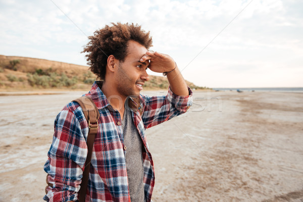 Concentrated african man standing outdoors and looking far away Stock photo © deandrobot