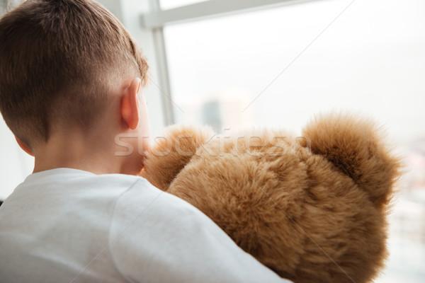 Alone little sad boy standing with teddy bear near window Stock photo © deandrobot