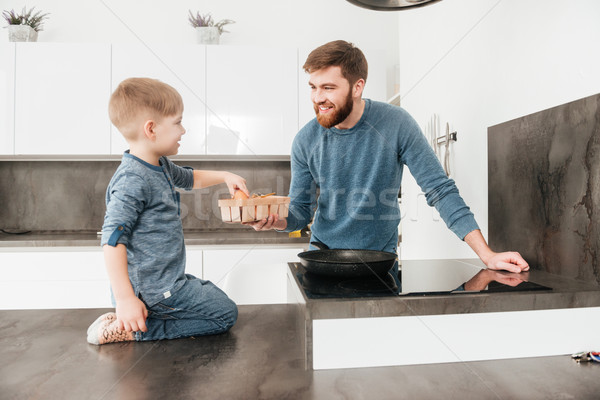 Bearded father cooking at kitchen with his little cute son Stock photo © deandrobot