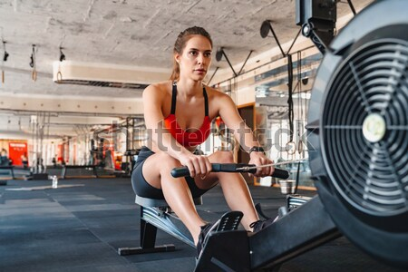 Fitness woman working out using exercise equipment in gym Stock photo © deandrobot