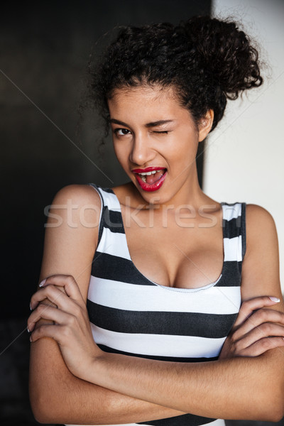 Lovely playful african american young woman standing and winking Stock photo © deandrobot