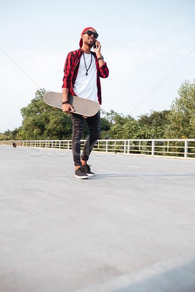 Dark skinned boy holding skateboard and talking on his phone Stock photo © deandrobot