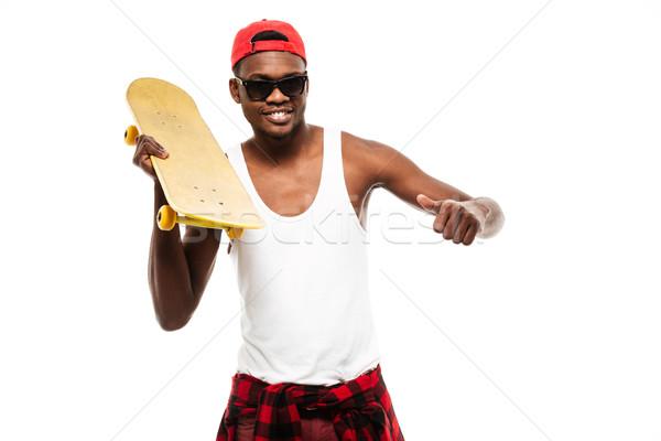 Mosolyog afrikai fiatalember tart gördeszka mutat Stock fotó © deandrobot
