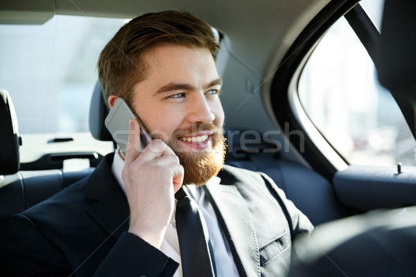 Smiling happy business man talking on mobile phone Stock photo © deandrobot