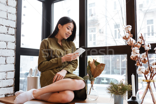 Stock photo: Cheerful asian young lady chatting by her mobile phone.