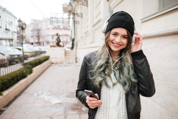 Glimlachende vrouw warm kleding luisteren muziek straat Stockfoto © deandrobot