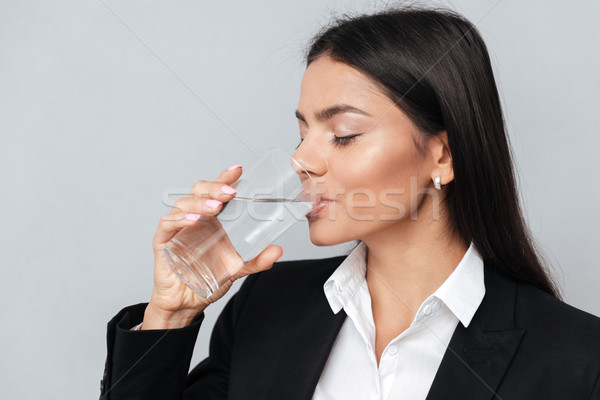 Business woman drinking water from a glass with eyes closed Stock photo © deandrobot