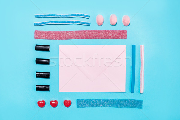 Group of tasty colorful sugar candies and blank paper envelope Stock photo © deandrobot