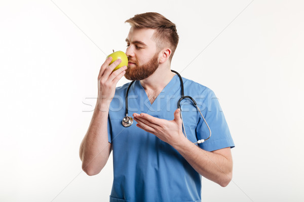 Portrait of healthy doctor smelling an apple and pointing Stock photo © deandrobot