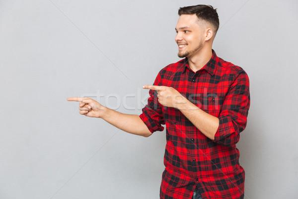 Smiling man pointing away Stock photo © deandrobot