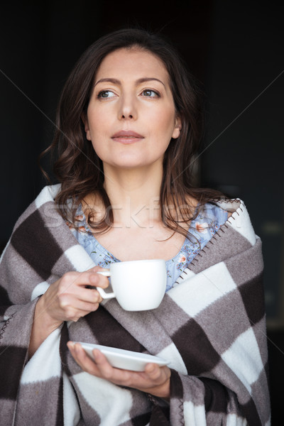 Concentrated woman in plaid standing indoors Stock photo © deandrobot