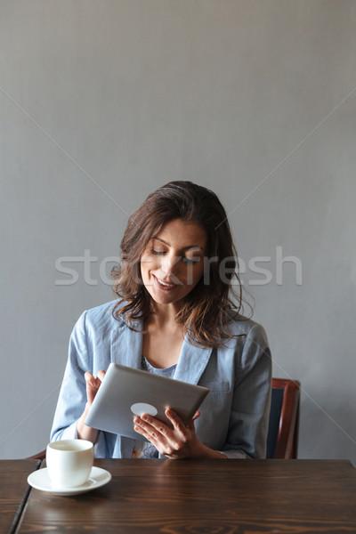улыбающаяся женщина сидят изображение глядя Сток-фото © deandrobot