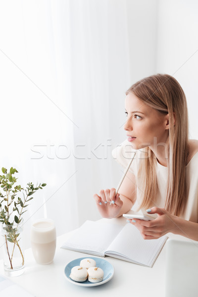 Woman sitting indoors near sweeties holding mobile phone. Stock photo © deandrobot
