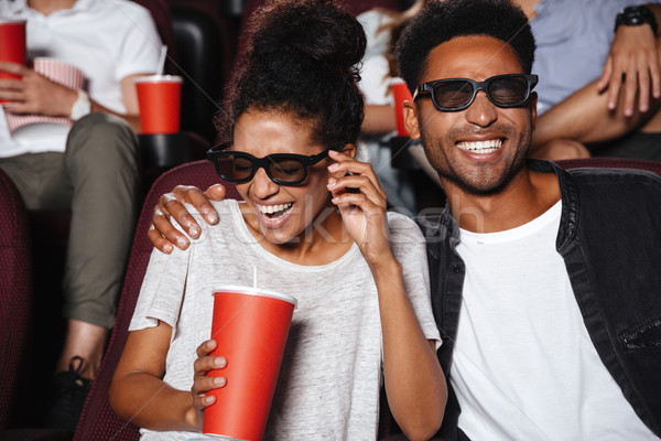 Attractive afro american couple watching 3D movie Stock photo © deandrobot