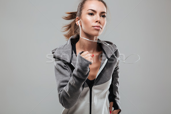 Concentrated female runner in warm clothes running Stock photo © deandrobot