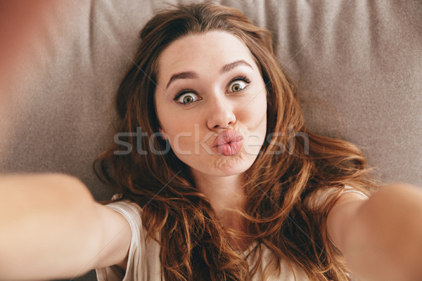 Funny pretty lady lies on sofa indoors make selfie. Stock photo © deandrobot