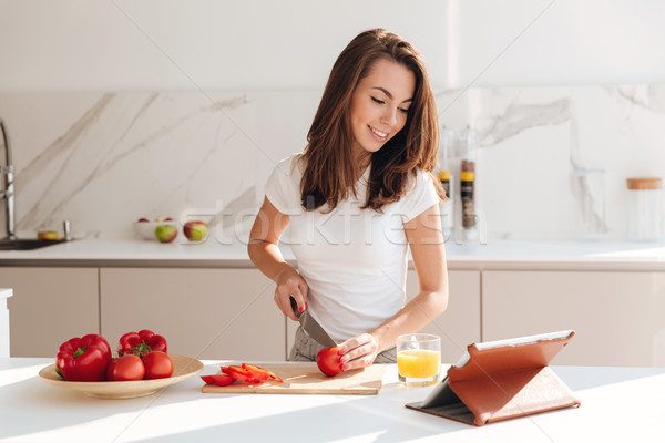 Happy young woman cutting vegetables for the salad Stock photo © deandrobot