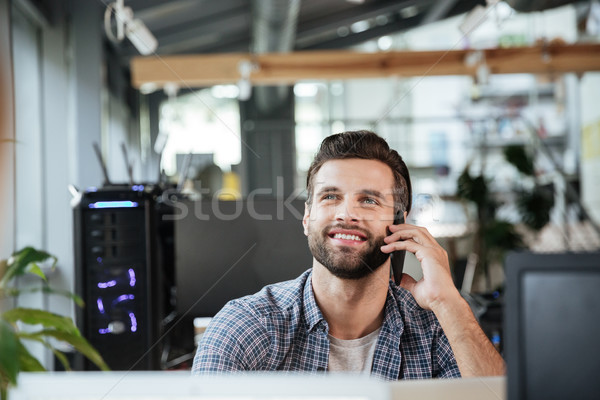 Man in office coworking while talking by mobile phone. Stock photo © deandrobot