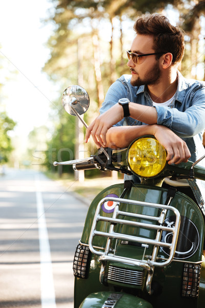 Concentrated young bearded man sitting on scooter outdoors Stock photo © deandrobot