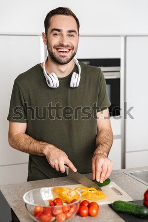 Joyful young guy cooking at home Stock photo © deandrobot