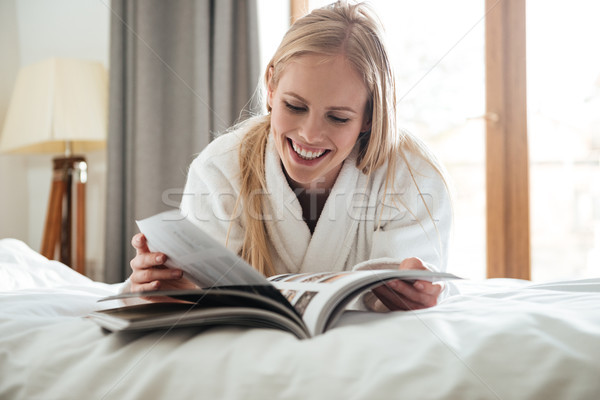 Young blonde woman reading magazine while lying on bed Stock photo © deandrobot