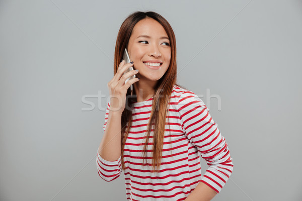 Portrait of a cheery asian girl talking on mobile phone Stock photo © deandrobot