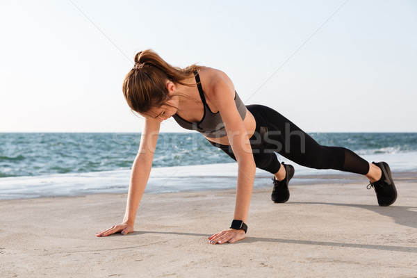 Photo of young female athlete standing in a plank position at th Stock photo © deandrobot