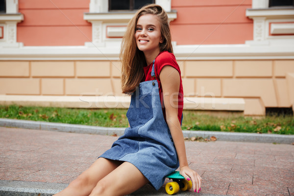 Smiling young teenage girl sitting on a skateboard Stock photo © deandrobot