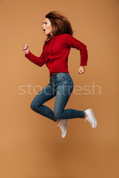 Full length photo of attractive young woman jumping hight over b Stock photo © deandrobot