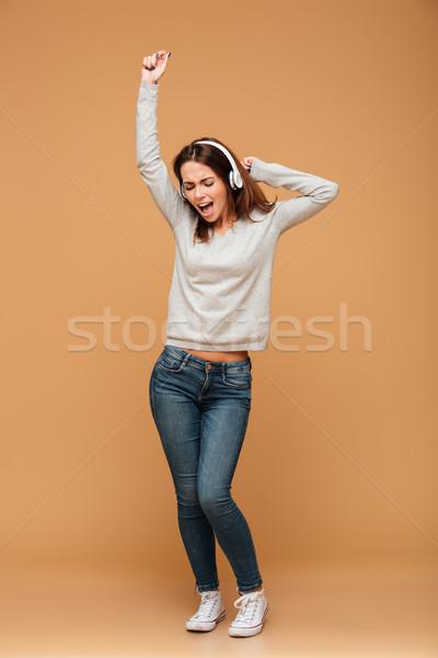 Full length photo of joyful girl in casual wear dancing while li Stock photo © deandrobot