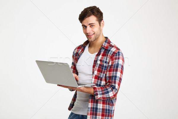 Portrait of a smiling young man holding laptop computer Stock photo © deandrobot