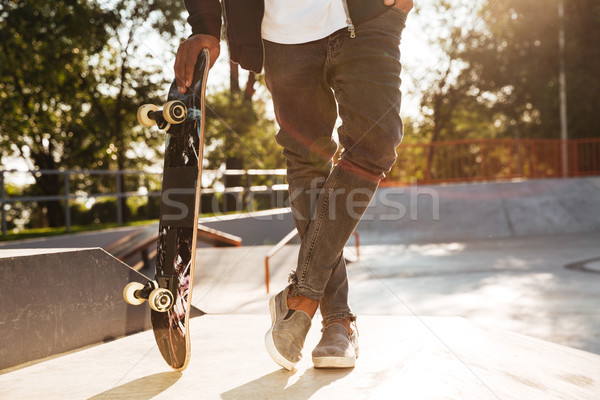 Cropped image of a young african man skateboarder Stock photo © deandrobot