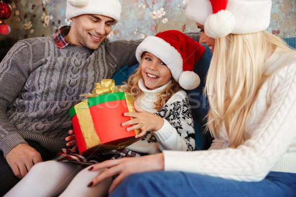 Happy little girl in Santa's hat holding present, looking at cam Stock photo © deandrobot