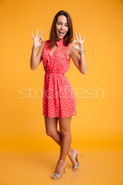 Full-length portrait of young elegant woman in red dress showing Stock photo © deandrobot