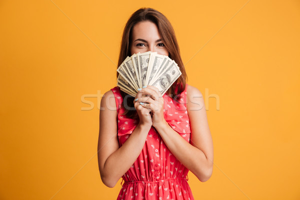 Young happy attractive woman in red dress hiding behind bunch of Stock photo © deandrobot