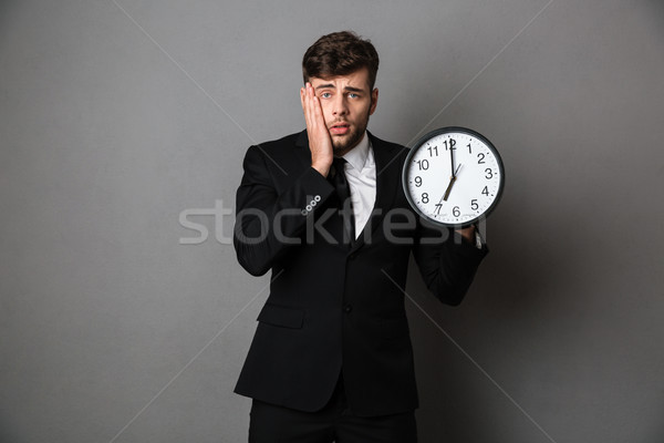 Close-up photo of upset worker in suit holding clock, looking at Stock photo © deandrobot