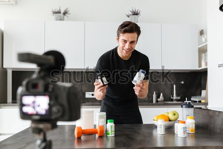 Excited young man filming his video blog episode Stock photo © deandrobot