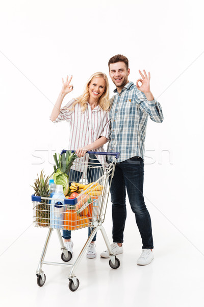 Full length portrait of a cheery couple Stock photo © deandrobot