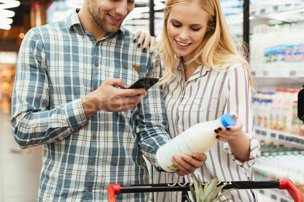 Couple in supermarket reading shopping list Stock photo © deandrobot