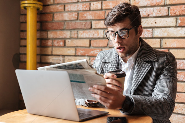 Shocked business man in eyeglasses sitting by table Stock photo © deandrobot