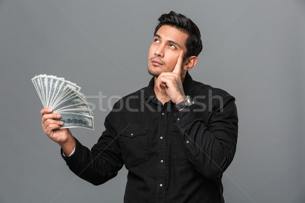 Young thinking concentrated man holding money. Stock photo © deandrobot