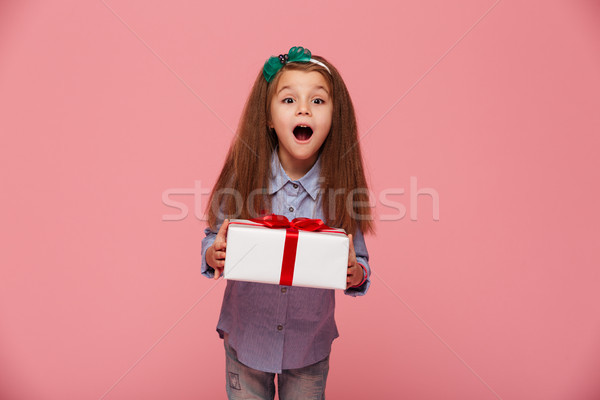 Joyous female kid shouting holding gift-wrapped box being excite Stock photo © deandrobot