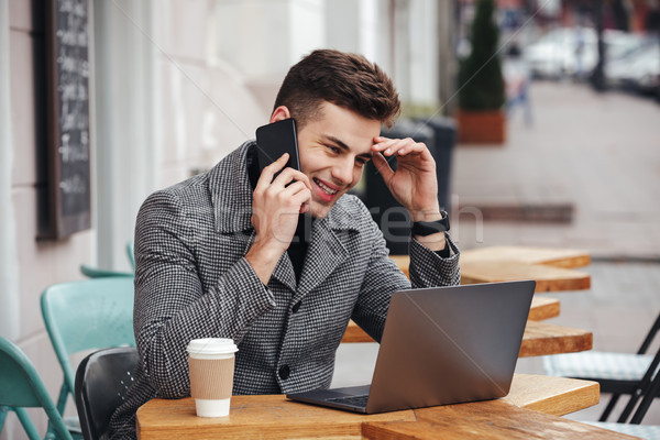 Portrait of content guy drinking takeaway coffee in street cafe, Stock photo © deandrobot