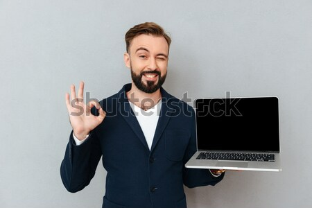 Picture of satisfied bearded man holding silver notebook demonst Stock photo © deandrobot