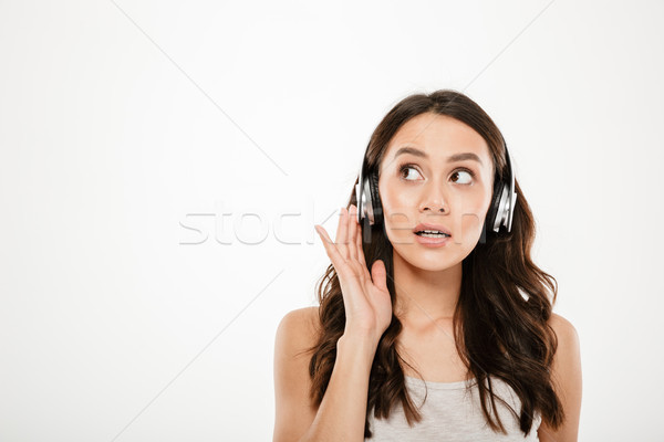 Mystery brunette woman in headphones listening music and looking away Stock photo © deandrobot