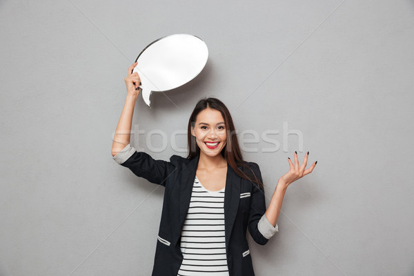 Happy surprised asian business woman holding blank speech bubble Stock photo © deandrobot