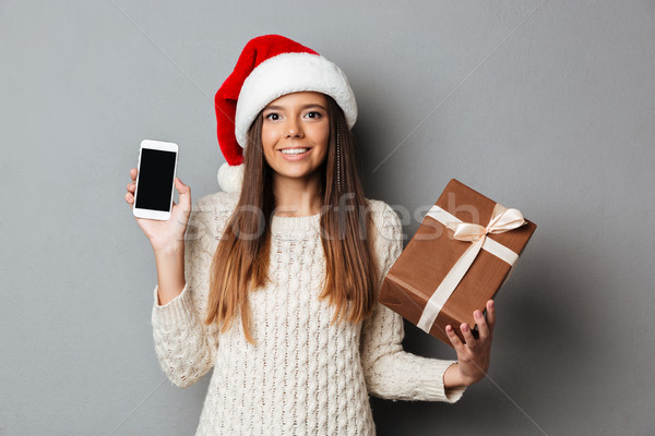 Happy brunette woman in sweater and christmas hat holding gift Stock photo © deandrobot